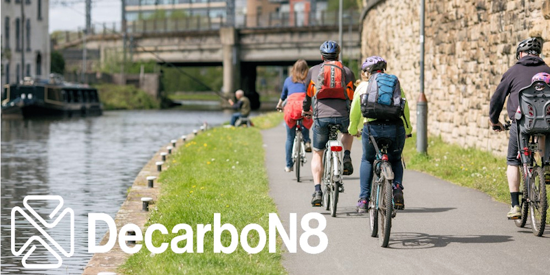 People cycling next to a canal with DecarboN8 logo watermark