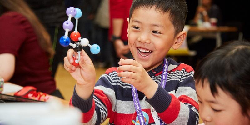 Kid holding a model of a molecule in his hand
