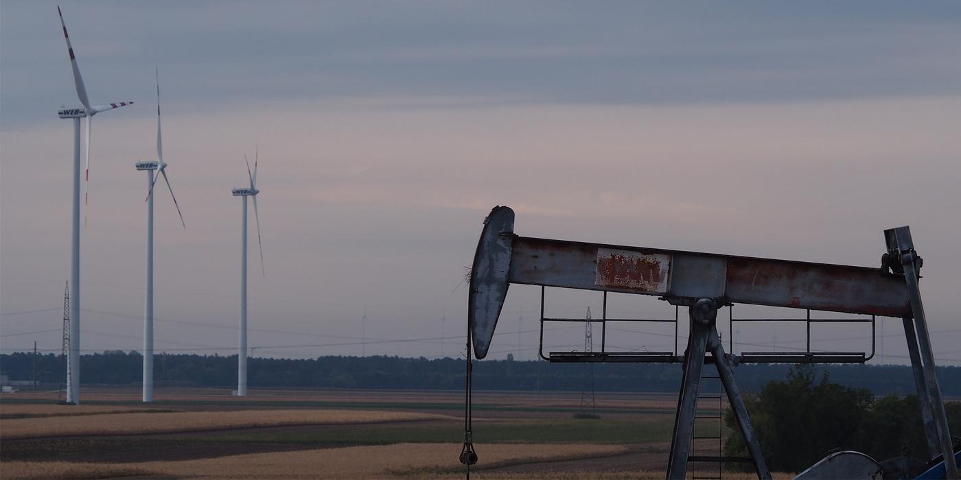 Image of an oil rig with a wind farm in the background
