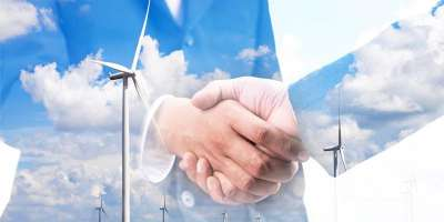 Stock image of two business men shaking hands with low transparency, over the image is a wind farm.