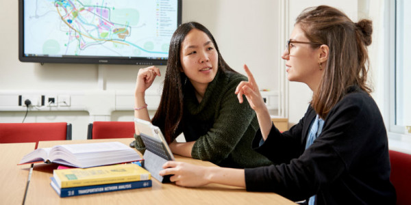 Two female-presenting students study together at a desk with a tablet, books and a large map on a screen in the background