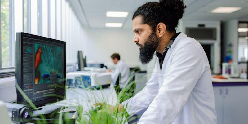Researcher in a laboratory wears a white coat and reads from a screen at the University of Leeds