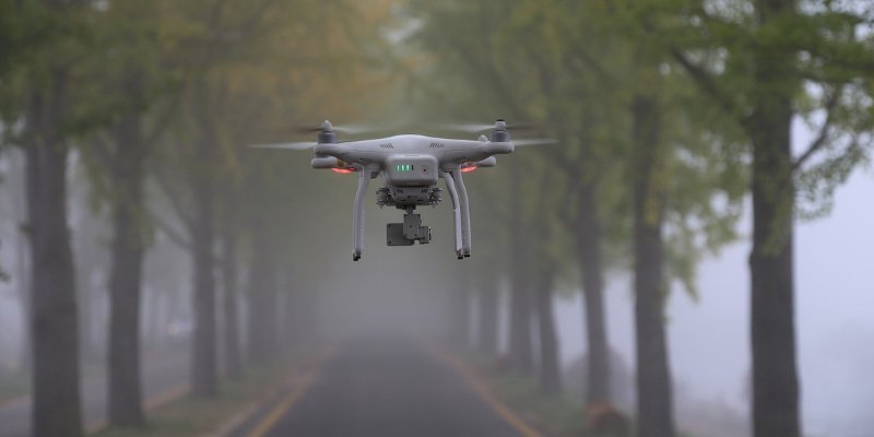 Image of a drone in the air, around a foggy road.